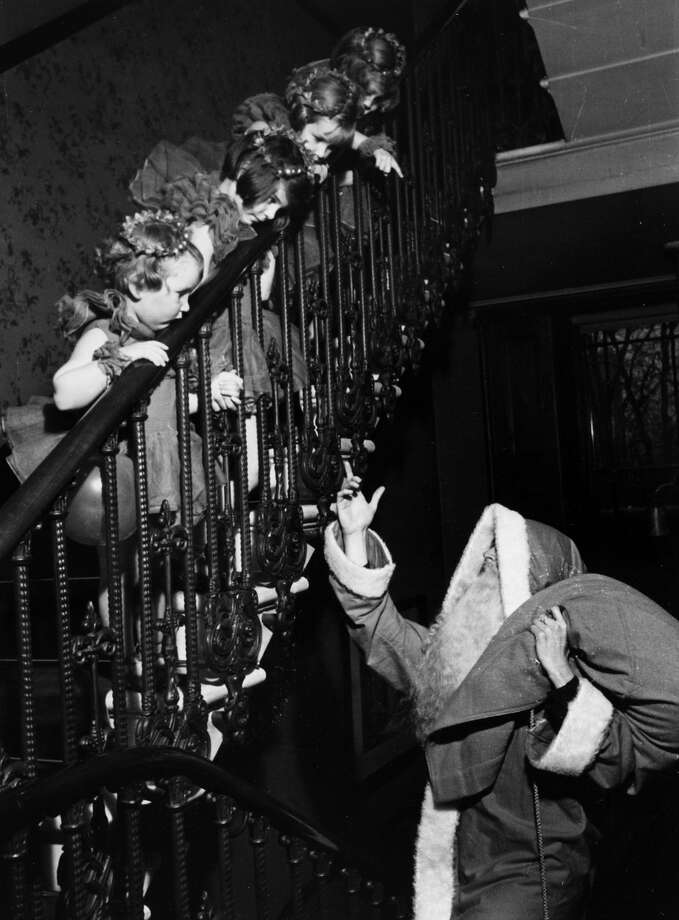 Father Christmas arrives at a Christmas party as children wait in wonder on the stairs, circa 1935. Photo: Popperfoto, Getty Images / Popperfoto