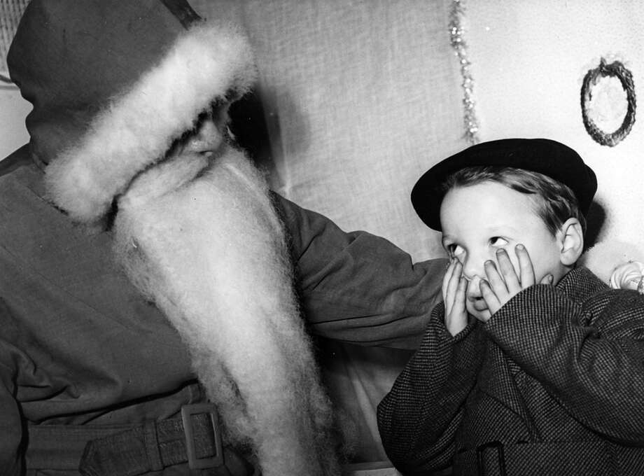 Father Christmas is paid a visit by a small boy who seems a frightened, as he peeps past his hands, circa 1957. Photo: Popperfoto, Getty Images / Popperfoto