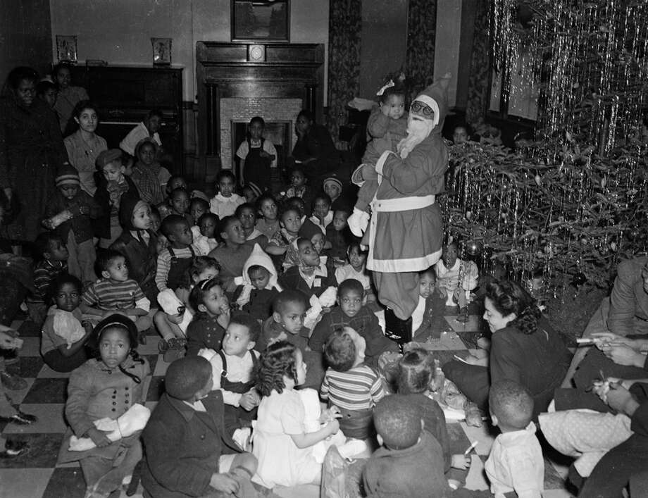 Toni McKamey dressed as Santa Claus holds child, surrounded by children seated on floor and a Christmas tree at the Centre Avenue YWCA in Pittsburgh in December 1941. Photo: Teenie Harris Archive/Carnegie Museum Of Art, Getty Images / Carnegie Museum of Art