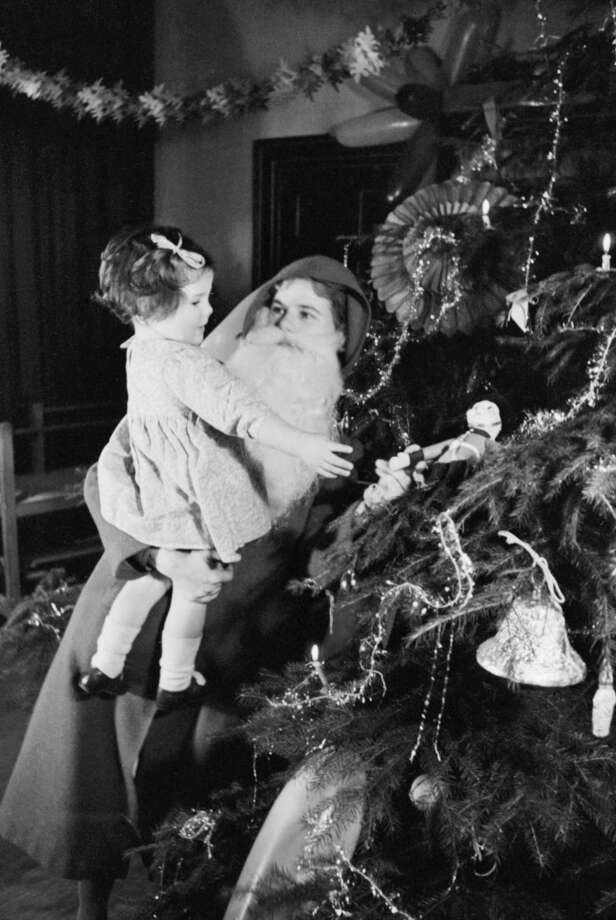 Father Christmas lifts a young girl up to look at a toy soldier on a highly-decorated Christmas tree at a home for evacuees in Henley-on-Thames, Oxfordshire, United Kingdom in December 1941. It is interesting to note that this Father Christmas is actually being played by a woman! Photo: IWM/Getty Images, Getty Images / IWM (D 5699)
