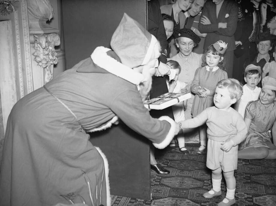 Father Christmas in a costume and mask presents a young boy with a gift of a book of nursery rhymes while shaking his hand at a Christmas party for Allied Naval Officers' Children in London on Dec. 17, 1942. Photo: IWM/Getty Images, Getty Images / IWM (A 13308)