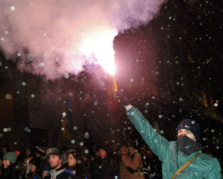 A Ukrainian student lights a flare during an opposition protest rally in Kiev on Thursday as President Viktor Yanukovych told the West to stay out of Ukraine's political crisis. Photo: AFP/Getty Images / AFP ImageForum