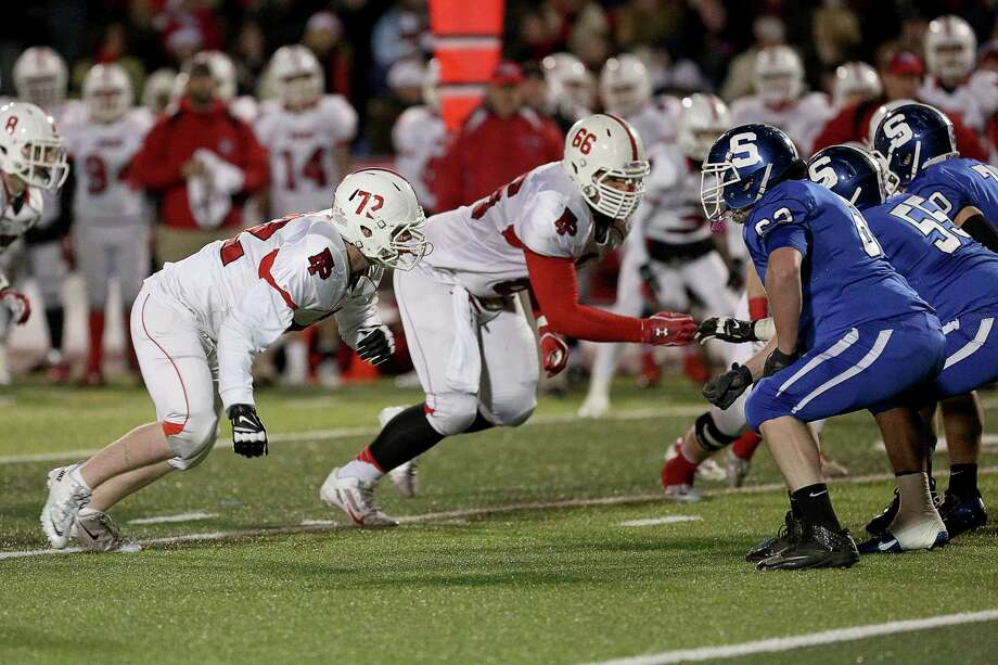 Fairfield Prep's # 72 William Lashar and #66  JAnthony Palazzolo go head to head against Southington High School offense during Thursday evening CIAC Class LL football championship game. Southington would win 52-34. Photo: Mike Ross / Mike Ross Connecticut Post freelance - @www.mikerossphoto.com