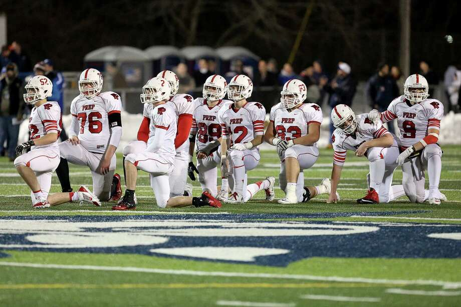 Fairfield Prep's offense team take a knee during injury timeout for team mate # 15 John DelliSanti during Thursday evening CIAC Class LL football championship game against Southington High School. Southington would win 52-34. Photo: Mike Ross / Mike Ross Connecticut Post freelance - @www.mikerossphoto.com