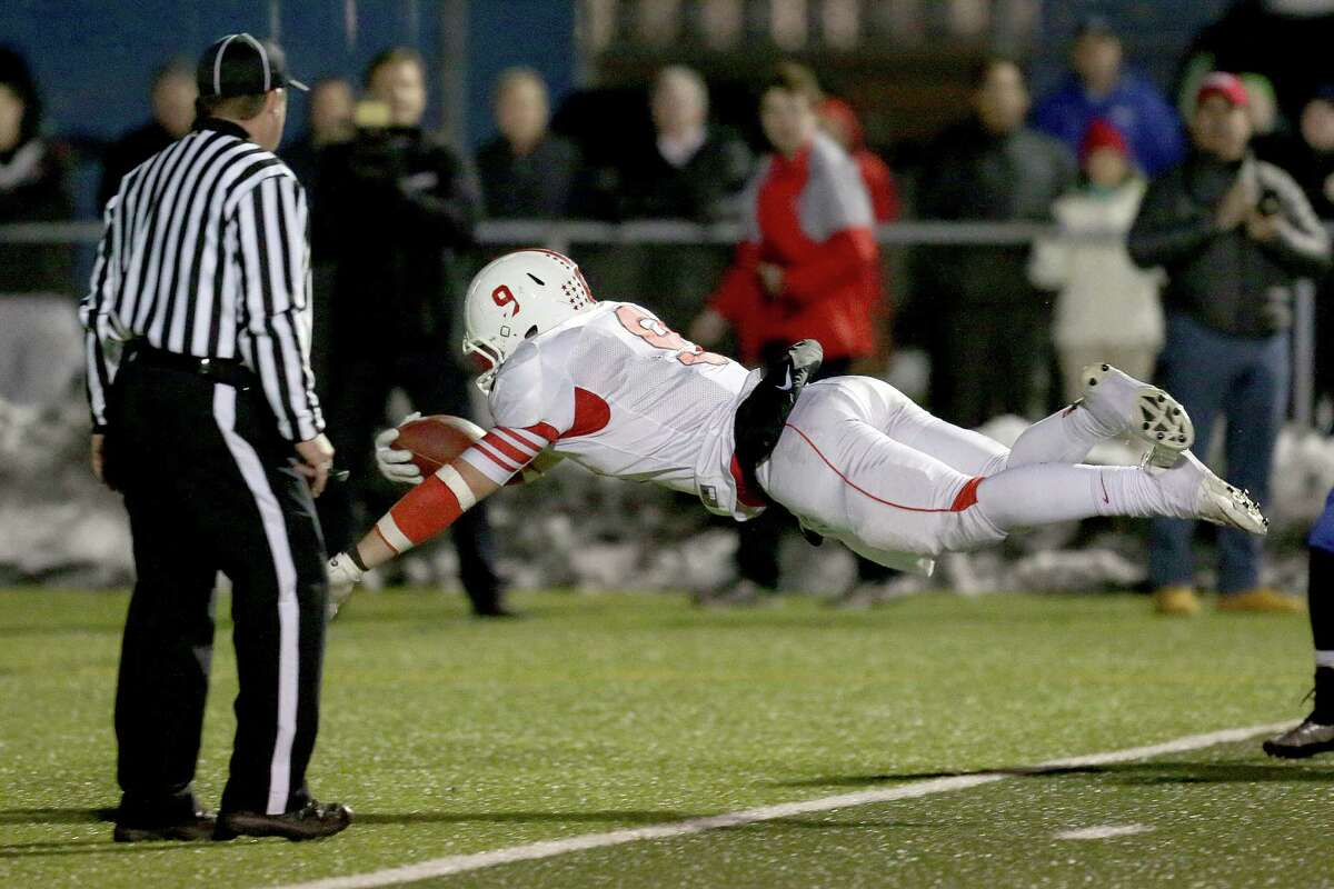 Fairfield Prep's # 9 Anthony Johnson dives into the endzone for a touch down during Thursday evening CIAC Class LL football championship game against Southington High School. Southington would win 52-34.