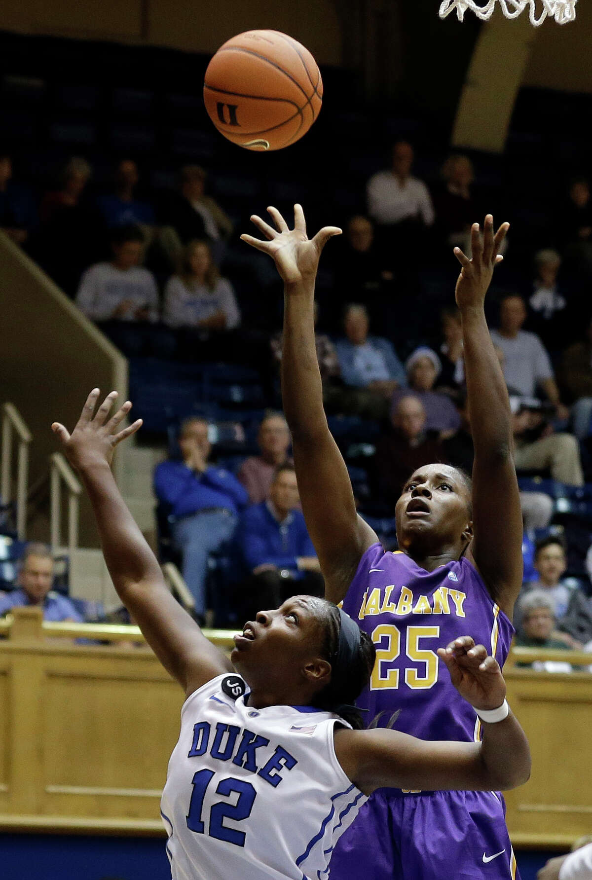 Duke's Chelsea Gray (12) defends as Albany's Shereesha Richards (25) shoots during the second half of an NCAA college basketball game in Durham, N.C., Thursday, Dec. 19, 2013. Duke won 80-51. (AP Photo/Gerry Broome) ORG XMIT: NCGB106