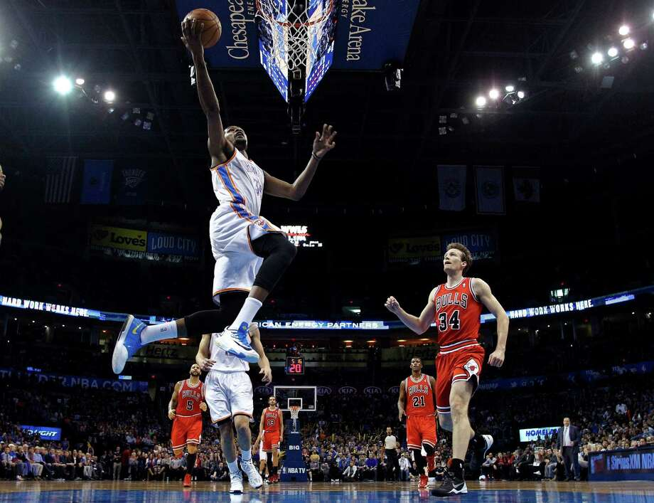 Oklahoma City Thunder forward Kevin Durant (35) shoots in front of Chicago Bulls forward Mike Dunleavy (34) during the first quarter of an NBA basketball game in Oklahoma City, Thursday, Dec. 19, 2013. (AP Photo/Sue Ogrocki) ORG XMIT: OKSO104 Photo: Sue Ogrocki / AP