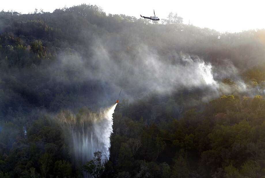 A helicopter makes a water drop on Pfeiffer Ridge above Fernwood in Big Sur, Calif., on Thursday, Dec. 19, 2013. Rain and higher humidity on Thursday helped firefighters battling the wildfire in the Big Sur region that has destroyed an estimated 22 homes. (AP Photo/Monterey County Herald, David Royal) Photo: David Royal, Associated Press