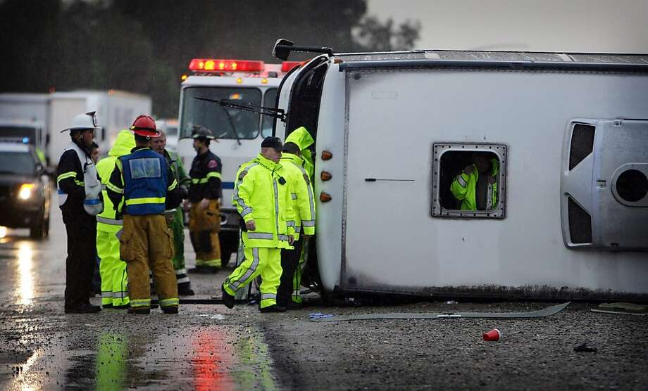 Emergency crews examine the scene of a tour bus that crashed and overturned on northbound Interstate 15 near Magnolia, on Thursday, Dec. 19, 2013, in Corona, Calif. Three bus crashes on Thursday killed one person and injured dozens more as the vehicles crashed or overturned on rain-slick Southern California freeways, authorities said. (AP Photo/The Press-Enterprise, Terry Pierson) Photo: Terry Pierson, Associated Press