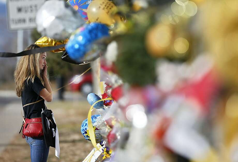 Arapahoe High School student body vice president Grace Marlowe looks at a tribute site for severely wounded student Claire Davis, who was shot by a classmate during a school attack six days earlier at Arapahoe High School, in Centennial, Colo., Thursday Dec. 19, 2013. On Thursday, students were allowed back into school to retrieve their belongings. (AP Photo/Brennan Linsley) Photo: Brennan Linsley, Associated Press