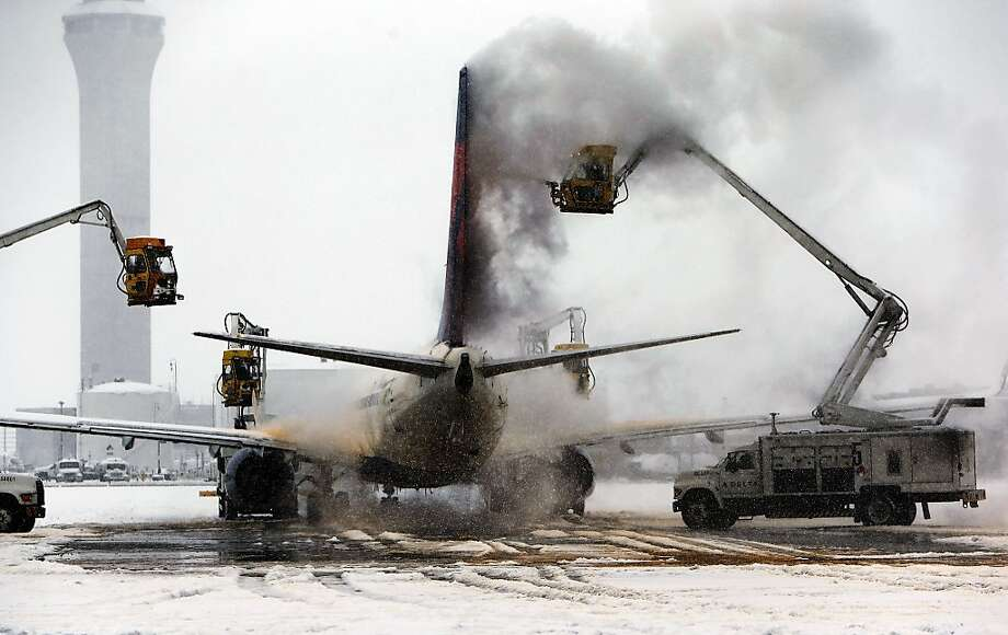 A jet is de-iced at Salt Lake City International Airport,  Thursday, Dec. 19, 2013 in Salt Lake City, Utah. A winter storm blasted northern Utah on Thursday, causing power outages, dozens of traffic accidents and the temporary shutdown of Salt Lake's airport after a cargo plane slipped on a runway. (AP Photo/The Salt Lake Tribune, Ravell Call)  DESERET NEWS OUT; LOCAL TV OUT; MAGS OUT Photo: Ravell Call, Associated Press