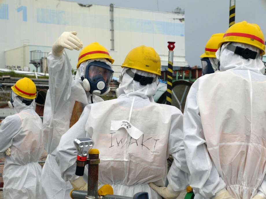 Members of International Expert Group (IEG) confer with a Tokyo Electric Power Co. official, center, as they inspect the decommissioning progress near the Unit 1 building at the crippled Fukushima Dai-ichi nuclear power plant in Okuma, Fukushima prefecture, northeast of Tokyo, during the first IEG meeting held from Sept. 23 - 27. It took until August this year, nearly two and half years after the tsunami, for Japan to set up the International Research Institute for Nuclear Decommissioning, to bring together ideas, both inside and outside Japan, on Fukushima decommissioning and encourage communication. Photo: The International Research Institute For Nuclear Decommissioning, ASSOCIATED PRESS