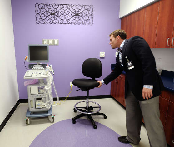 Garrett Syphrett, AVP of business development and operations, moves a chair near an ultrasound machine at the Altus Emergency Care Center on Thursday. Syphrett said the facility's examination table for the room was still on the way. The Altus Emergency Care Center on LHS Drive in Lumberton is scheduled to open on Friday morning, and will be the first hospital to operate in Hardin County since the 1990s. The facility will offer emergency medical care 24-hours a day, seven-days a week, and will include rooms for short-term observation. Photo taken Thursday, 12/19/13 Jake Daniels/@JakeD_in_SETX Photo: Jake Daniels / ©2013 The Beaumont Enterprise/Jake Daniels