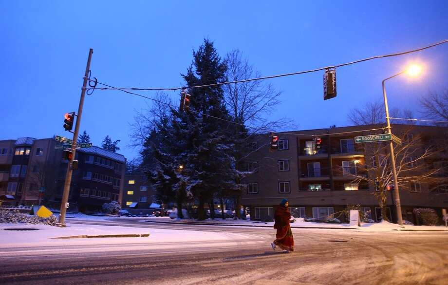 A woman crosses Northeast 125th Street at 8th Avenue Northeast as snow falls in Seattle. Photo: JOSHUA TRUJILLO, SEATTLEPI.COM STAFF