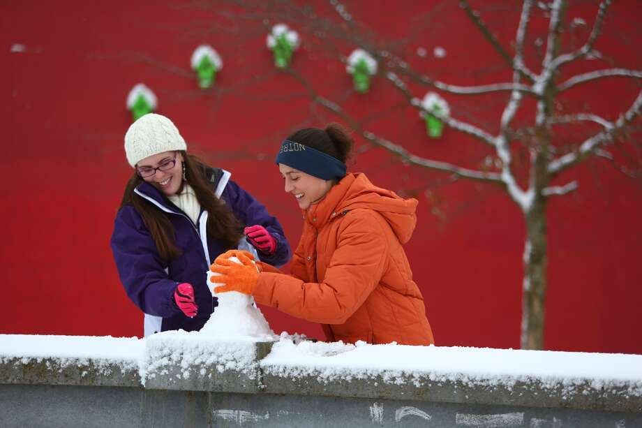 Anne Flinchbaugh, left, and Kaitlyn Buck make a snowman at Cal Anderson Park in Capitol Hill. Photo: JOSHUA TRUJILLO, SEATTLEPI.COM STAFF