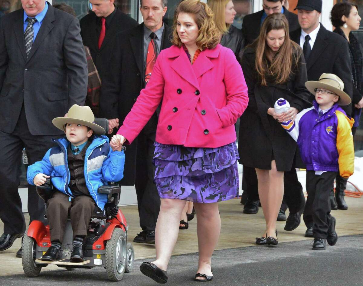 NYS Trooper David W. Cunniff's wife Amy, center and sons Caleb, 6, left, and Zachary, 5, arrive for funeral services at Grace Fellowship Church Friday Dec. 20, 2013, in Colonie, NY. (John Carl D'Annibale / Times Union)