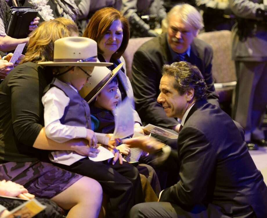Gov. Andrew Cuomo, right,  speaks with Zachary and Caleb Cunniff at the celebration of their father's life Friday morning, Dec. 20, 2013, at Grace Fellowship Church in Colonie, N.Y. Trooper David Cunniff was killed in an accident on the NYS Thruway Monday night while making a traffic stop near Amsterdam, N.Y. (Skip Dickstein / Times Union)
