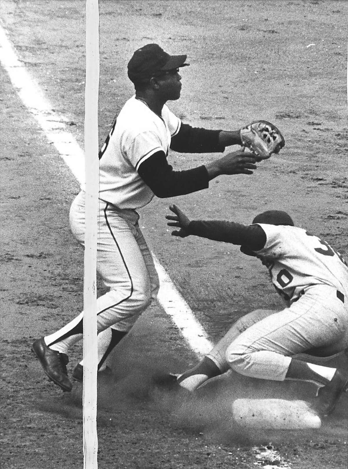 9-21-65- San Francisco- Three bases on a single. Los Angeles short stop Maury Wills eases into third base after hitting a single in the sixth inning of game today at San Francisco that got by Willie Mays, who tried to scoop it up in center field on the run. Third baseman Jim Hart wits patiently for the ball at third. It was the third error of the season for Mays. Willie scored on a single by Willie Davis before the inning ended.