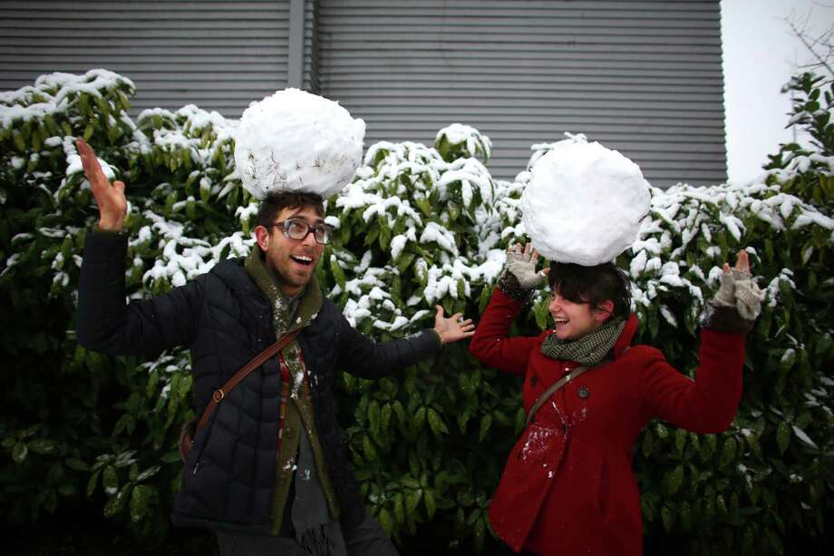 Timothy Firth and Whitney Bashaw try to balance snowballs as they walk on East Olive Street in Seattle's Capitol Hill neighborhood after measurable snow fell for the first time in two years in the city. Photo: JOSHUA TRUJILLO, SEATTLEPI.COM / SEATTLEPI.COM