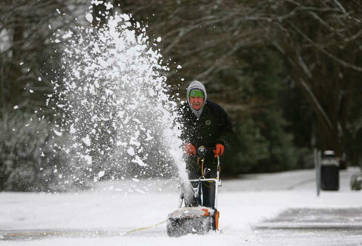 Jim Haarsager of the Seattle Art Museum cleans a sidewalk in front of SAM's Seattle Asian Art Museum at Volunteer Park after snow fell in Seattle on Friday, December 20, 2013.