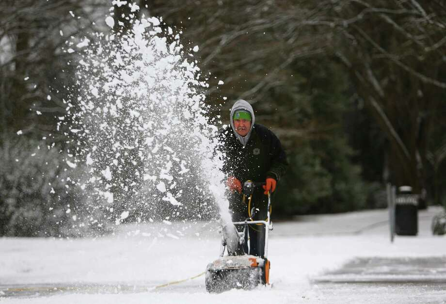 Jim Haarsager of the Seattle Art Museum cleans a sidewalk in front of SAM's Seattle Asian Art Museum at Volunteer Park after snow fell in Seattle on Friday, December 20, 2013. Photo: JOSHUA TRUJILLO, SEATTLEPI.COM / SEATTLEPI.COM