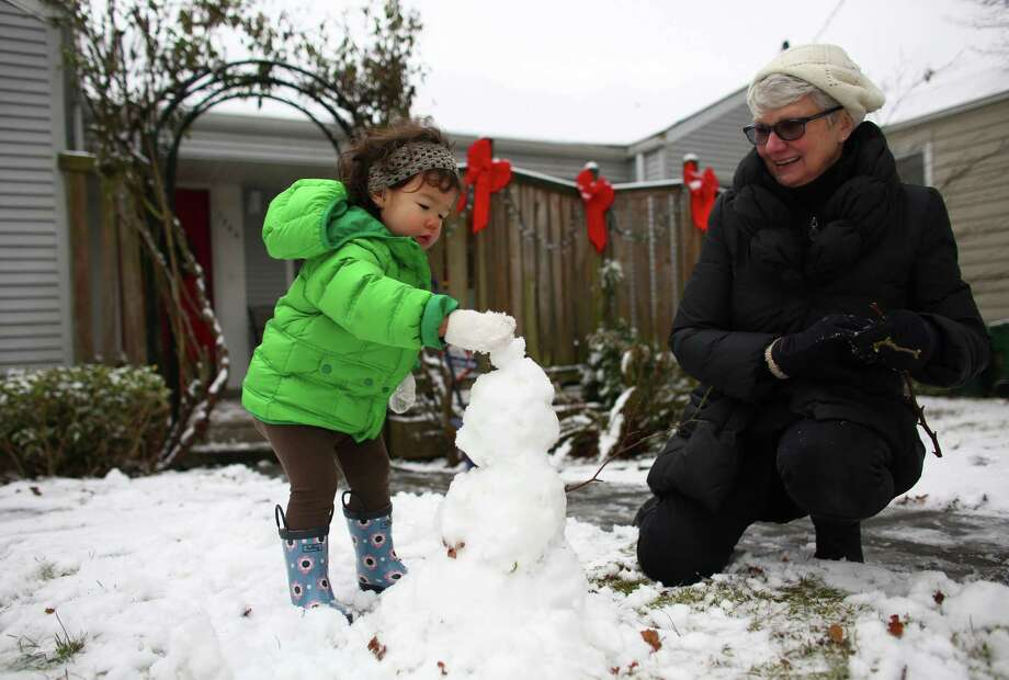 Lea Tsukimura, 2, checks out snow for the first time with her grandmother Mary Myers in the Ravenna neighborhood after snow fell in Seattle for the first time in two years on Friday, December 20, 2013. Photo: JOSHUA TRUJILLO, SEATTLEPI.COM / SEATTLEPI.COM
