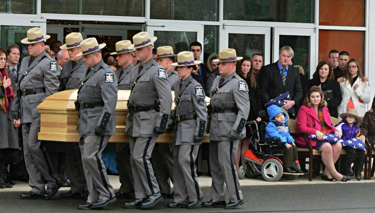 NYS Trooper David W. Cunniff's wife Amy, at right center and sons Caleb, 6, left, and Zachary, 5, watch as NYS Troopers carry Cunniff's casket during funeral services at Grace Fellowship Church Friday Dec. 20, 2013, in Colonie, NY. (John Carl D'Annibale / Times Union)