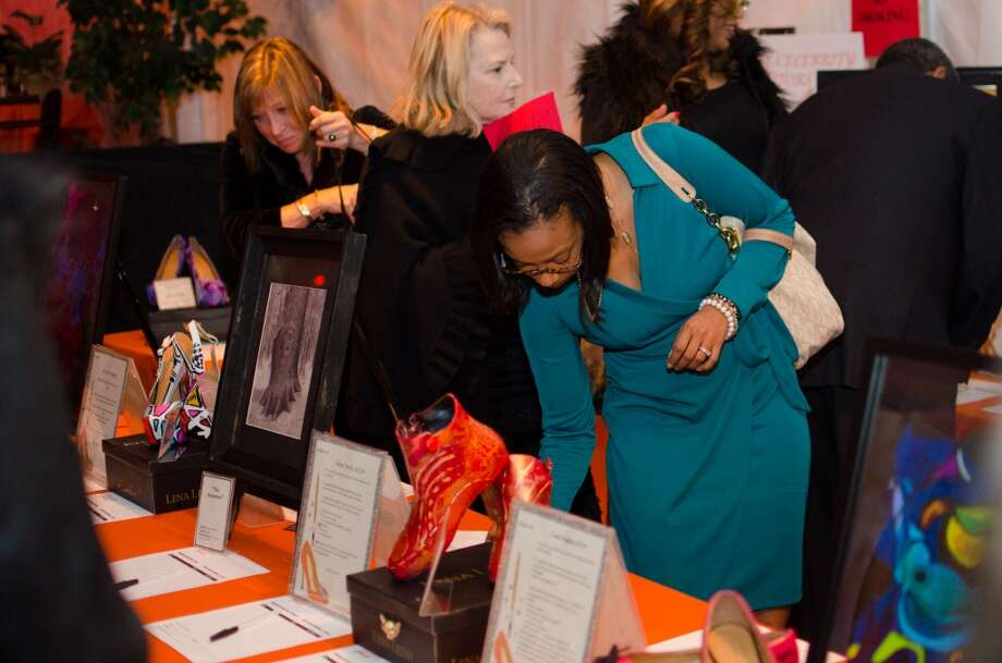 Kim Cunningham bids on an item in the silent auction during YWCA of Houston's Shoe Soiree Fundraiser. Photo: Jamaal Ellis, For The Chronicle