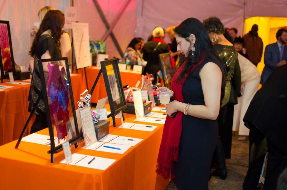Rashna Barge looking at items up for auction during YWCA of Houston's Shoe Soiree Fundraiser. Photo: Jamaal Ellis, For The Chronicle