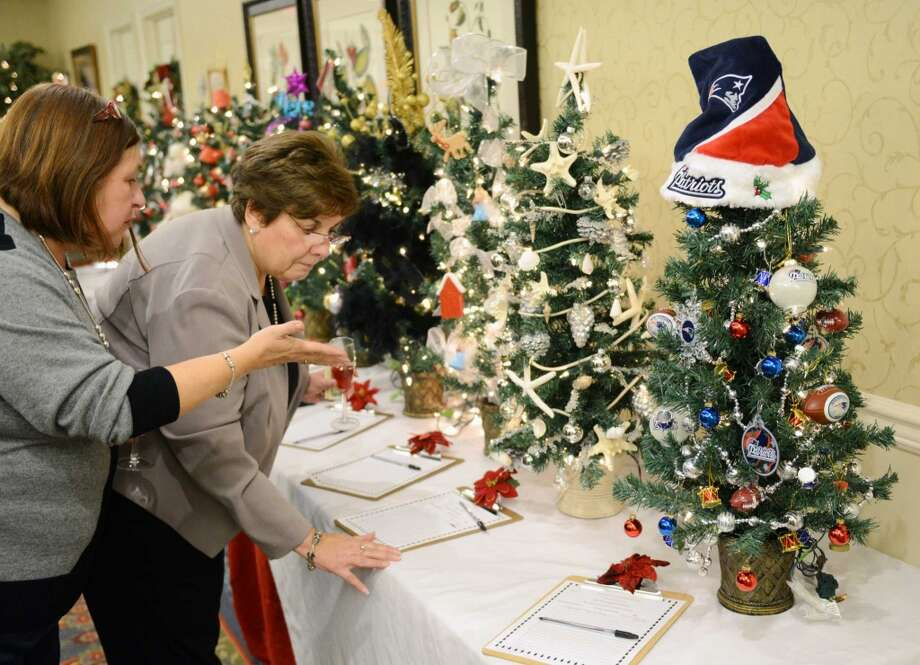 Newtown residents Sandy Cruz, left, and Sandy Smith look at the decorated miniature Christmas trees during the Festival of Trees at Maplewood Senior Living Center in Danbury, Conn. on Wednesday, Dec. 4, 2013.  This festival, now in its fourth year, featured a silent auction for 24 festive trees decorated by individuals and companies, with about $2,000 in proceeds going to the Alzheimer's Association.  About 75 people attended the event, which also included food, drinks and an arts and crafts sale. Photo: Tyler Sizemore, Danbury News-TImes