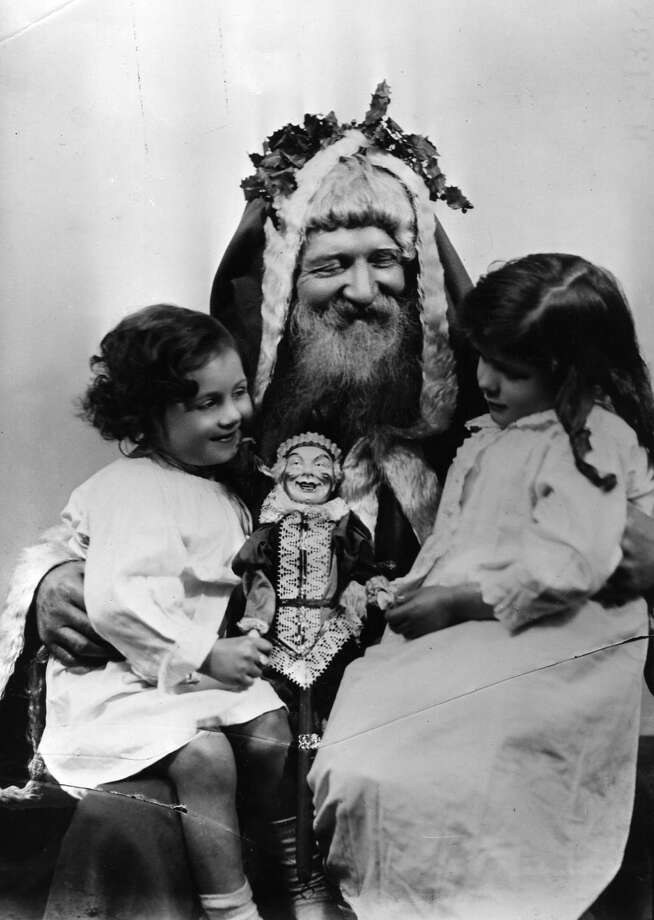 Santa Claus seems very pleased to be giving the two little girls a doll in Laplander clothes, circa 1918.