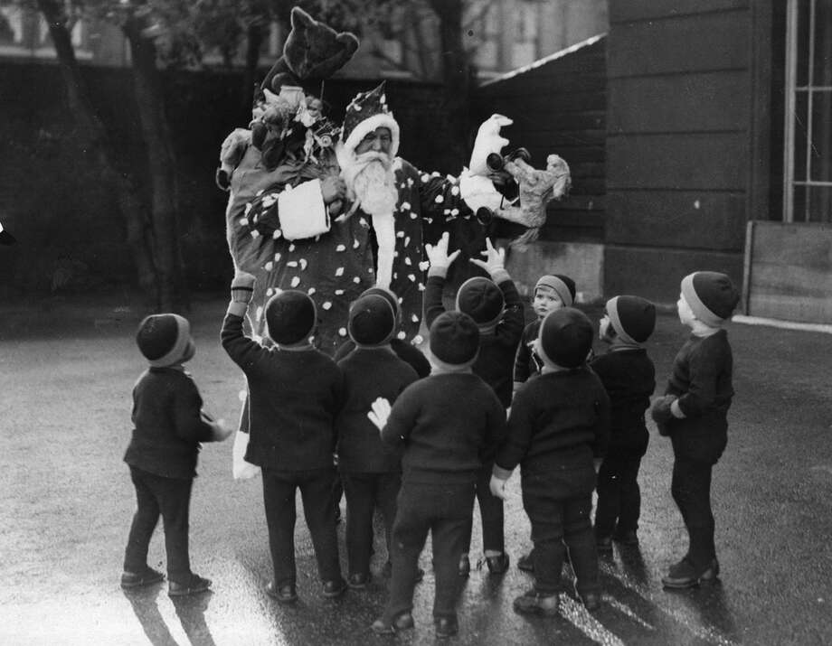 Santa Claus distributes gifts to homeless children at Leytonstone, London, on Dec. 22, 1933. Photo: Fox Photos, Getty Images / Hulton Archive