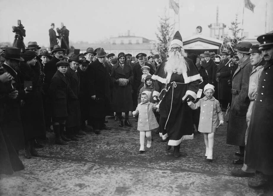 Saint Nicholas holds the hands of children on Dec. 6, 1933. Photo: KEYSTONE FRANCE, Getty Images / KEYSTONE FRANCE