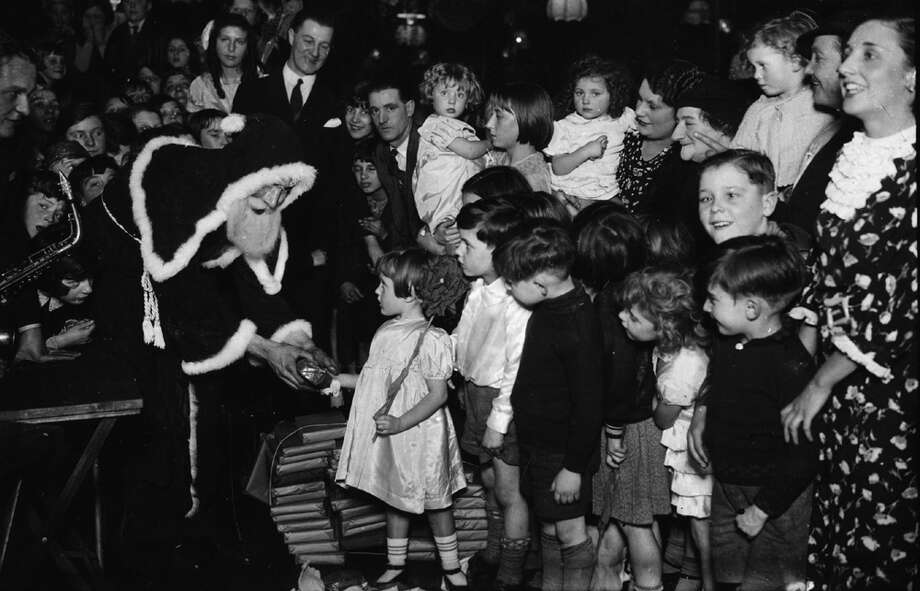 Santa Claus meets the children of Hammersmith at a Christmas party at Lane's Club, West London, Dec. 16, 1934. Photo: Topical Press Agency, Getty Images / Hulton Archive