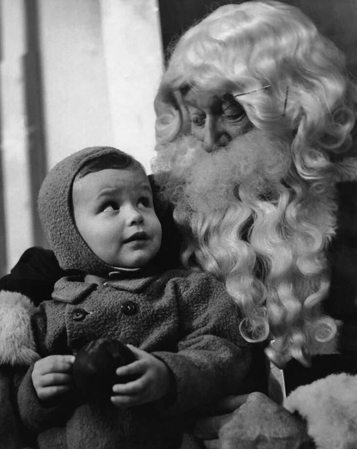 A small boy in a winter coat sits on the lap of a luxuriantly bearded Santa, circa 1935. Photo: Archive Photos, Getty Images / 2010 Getty Images