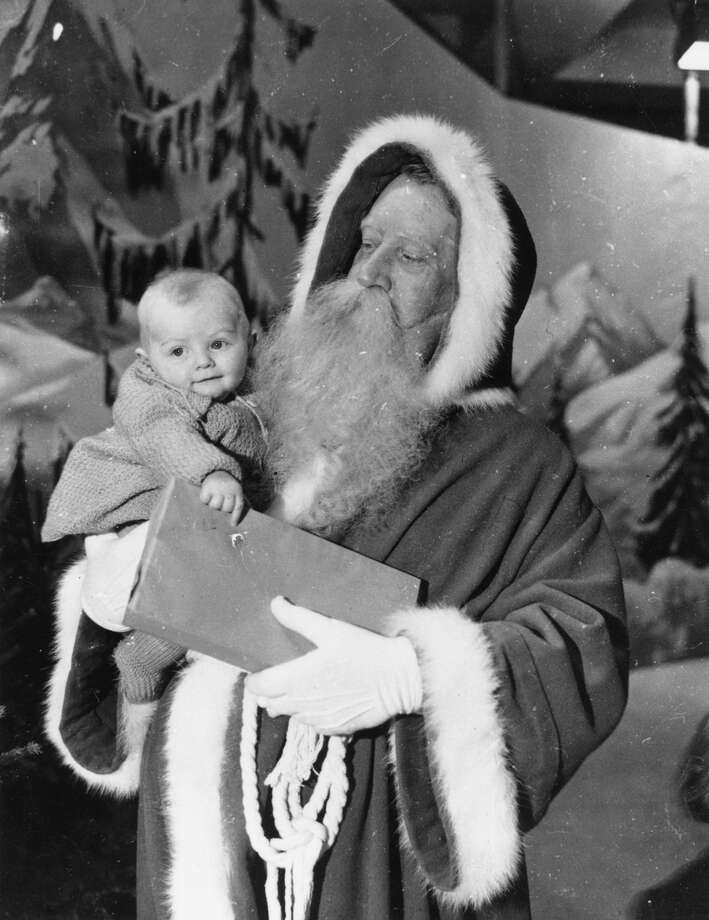 Santa Claus holds a small child and wrapped gift on Nov. 3, 1938. Photo: Topical Press Agency, Getty Images / Hulton Archive