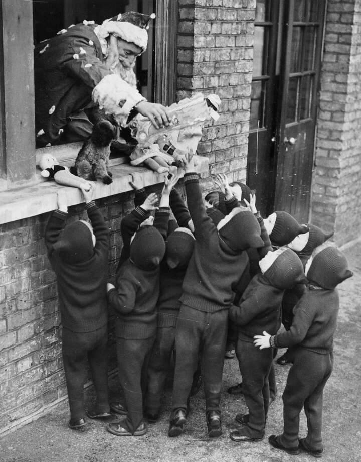 Father Christmas hands out presents to children at the Aid and Adoption Society home at Leytonstone, United Kingdom on Dec. 7, 1938. Photo: Gerry Cranham, Getty Images / Hulton Archive