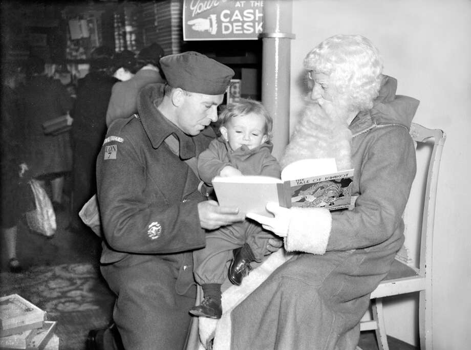 Father Christmas in a London store interests young 17-month-old Michael Cole in a fairy story book, while Michael's father, C.S.M. Cole of the Home Guard, lends a hand, Nov. 17, 1941. Photo: Planet News Archive, Getty Images / SSPL/Planet News Archive