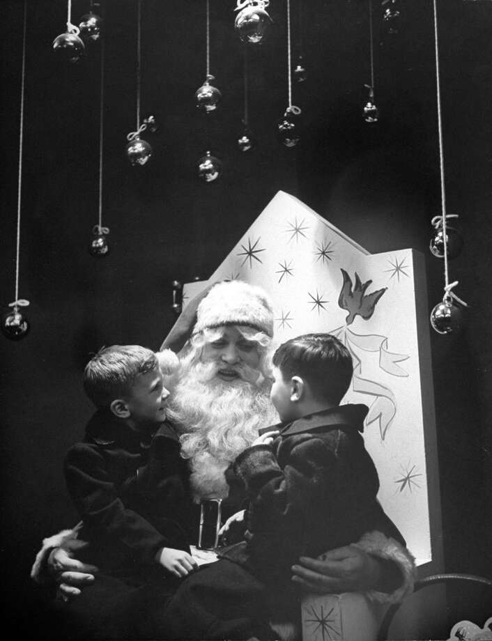 A department store Santa Claus talks with two boys sitting on his lap in 1943. Photo: Jerry Cooke, Getty Images / Time & Life Pictures