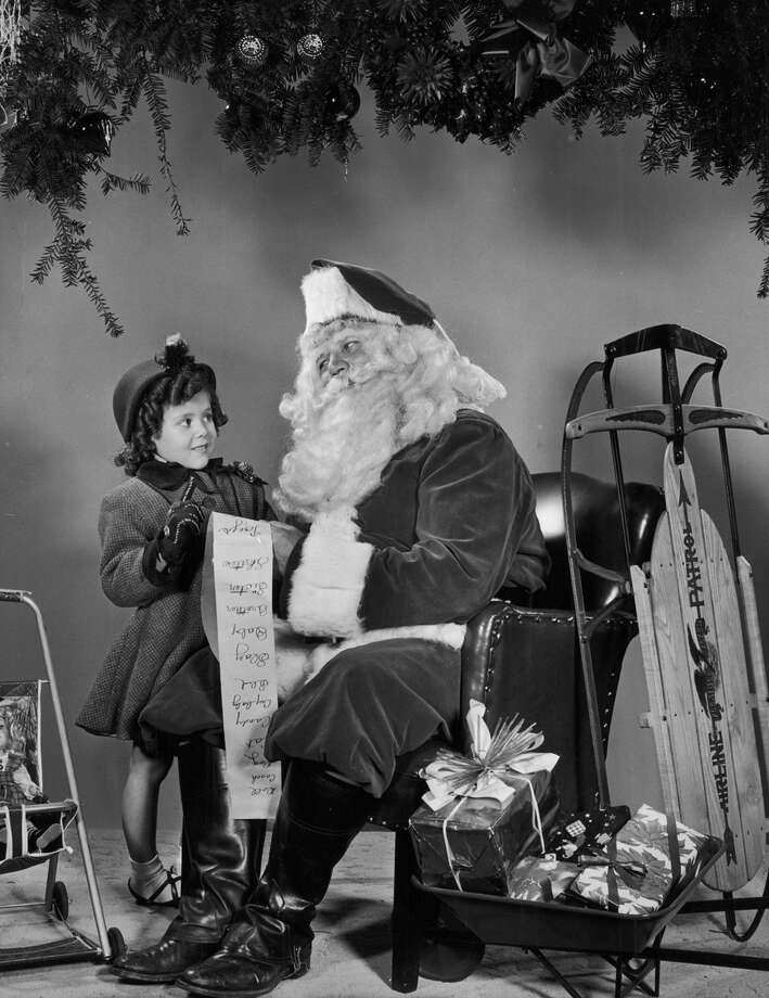 A little girl, wearing a winter coat, gives Santa Claus her wish list, circa 1945. Photo: Harold M. Lambert, Getty Images / Archive Photos
