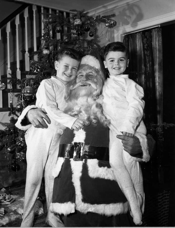 Santa Claus smiles as he hugs two young boys wearing pajamas in front of a decorated Christmas tree, circa 1945. Photo: Lambert, Getty Images / Archive Photos