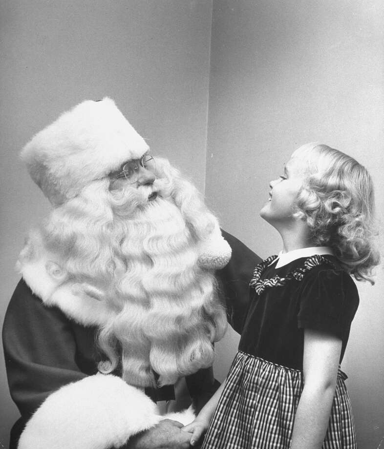 Santa Claus holds a little girl while she recites her Christmas list, circa 1948. Photo: Martha Holmes, Time & Life Pictures/Getty Images / Time Life Pictures