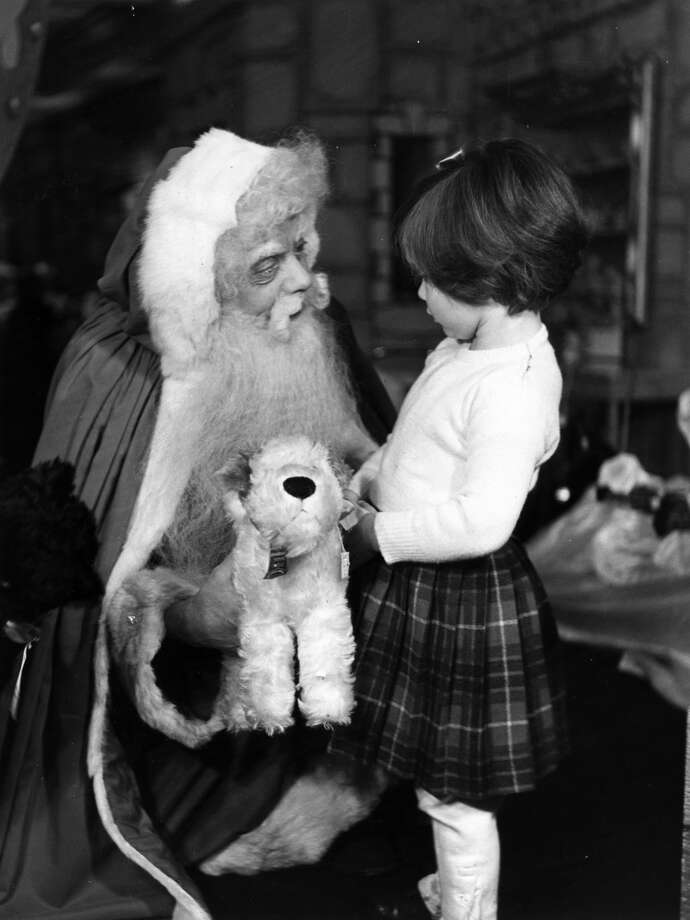 A little girl gets a toy dog from Father Christmas at a London store on Dec. 10, 1949. Photo: Elizabeth Chat, Getty Images / Picture Post