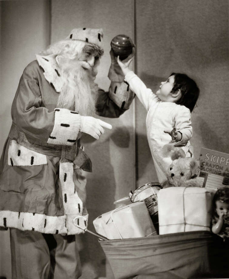 A little girl helps Santa Claus with his bag of toys, circa 1950. Photo: George Marks, Getty Images / Retrofile