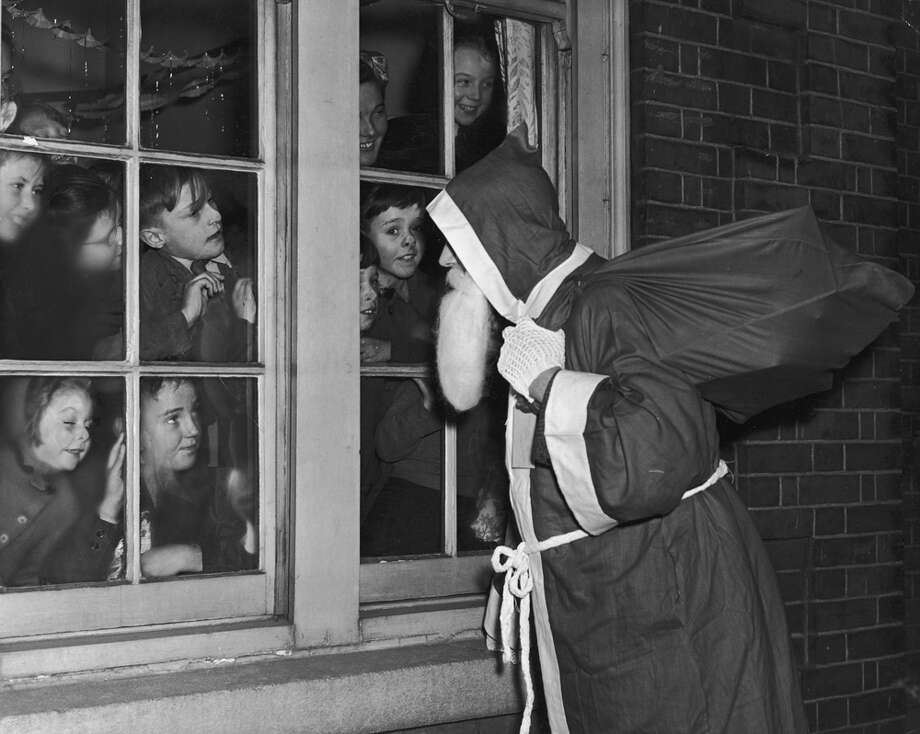 Father Christmas visits a group of children in East Ham, London, on Dec. 22, 1950. Photo: William Vanderson, Getty Images / 2009 Getty Images