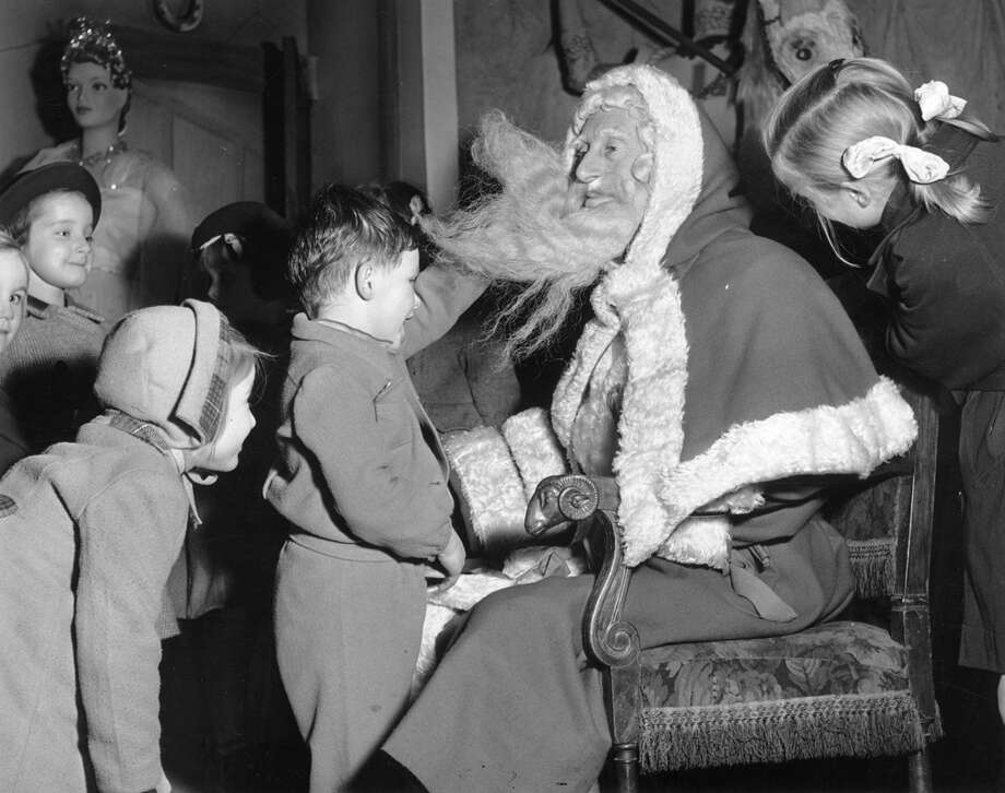 Bob Gordon, a department store Father Christmas, has some close shaves with the slightly more curious children, such as this young boy intent on discovering the secret under Santa's beard, on Nov. 30, 1951. Photo: Chris Ware, Getty Images / Hulton Archive