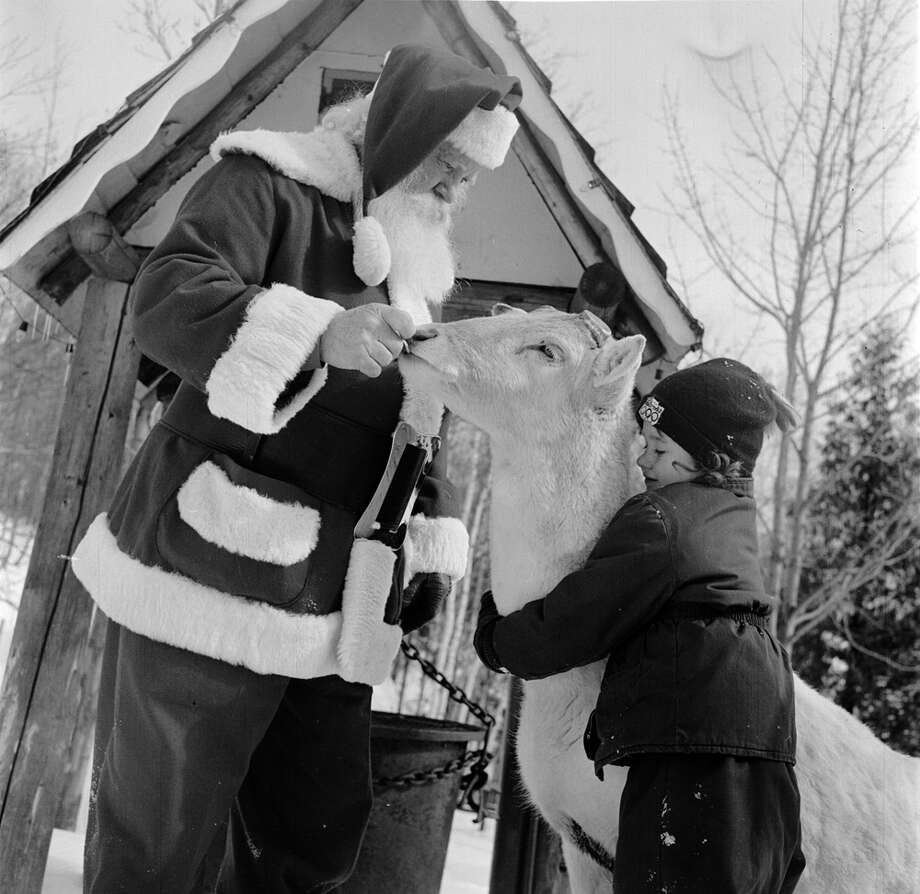 Santa Claus introduces a young visitors to one of his reindeer at his North Pole Workshop in the Adirondack Mountains of New York State, circa 1955. Photo: Orlando, Getty Images / Hulton Archive
