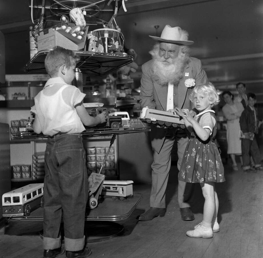 Santa impersonator Lucky Squires takes two children around a New York toy shop at the start of the Christmas season, circa 1955. Photo: Three Lions, Getty Images / Hulton Archive