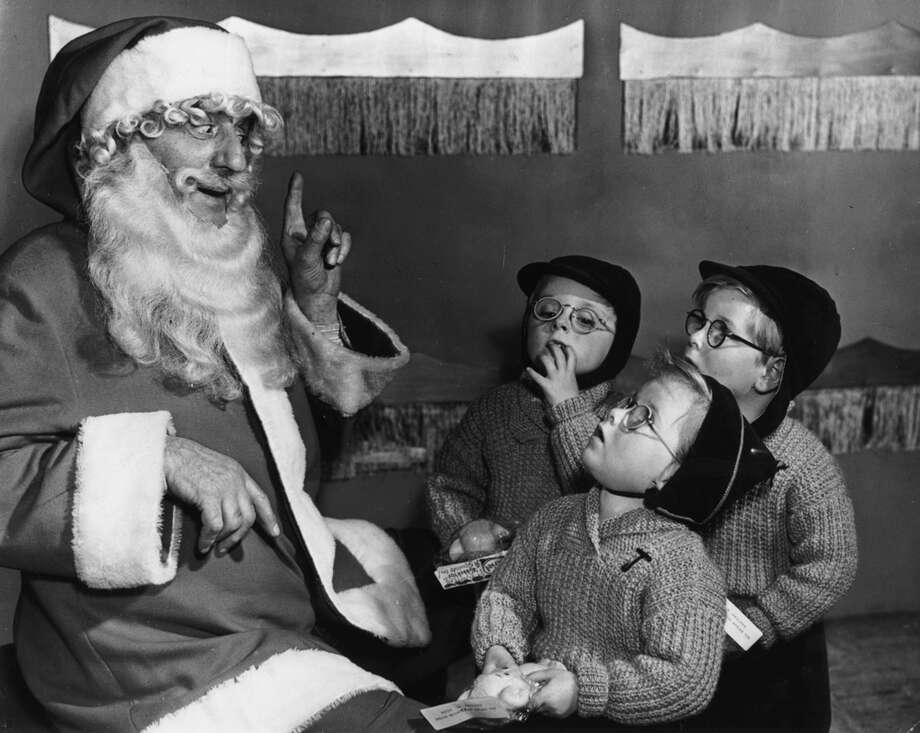 Santa Claus talks with the three-and-a-half-year-old Beech triplets at Bentalls store in Kingston-on-Thames, United Kingdom, on Nov. 21 1956. Photo: Fox Photos, Getty Images / Hulton Archive