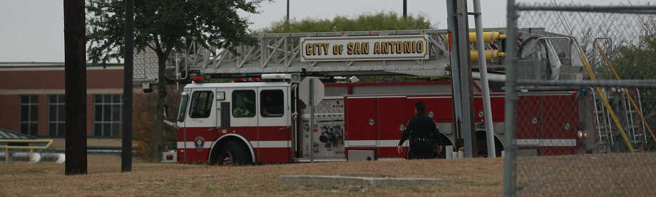 A police officer approaches a fire engine Friday December 20, 2013 by Stevens High School after a student climbed onto the school's roof. The incident caused a lockdown at the school and also at nearby Murnin Elementary School. Police spoke to the student and managed to bring him down and detain him. Photo: JOHN DAVENPORT, SAN ANTONIO EXPRESS-NEWS / ©San Antonio Express-News/Photo may be sold to the public
